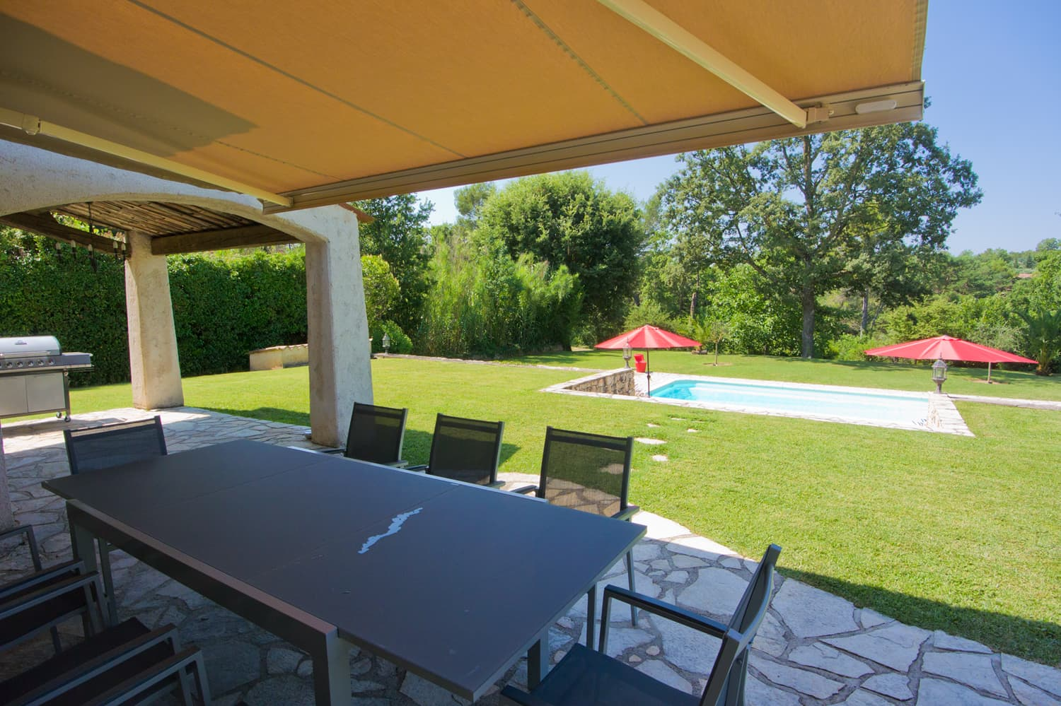 Shaded dining terrace with lawned garden and private pool