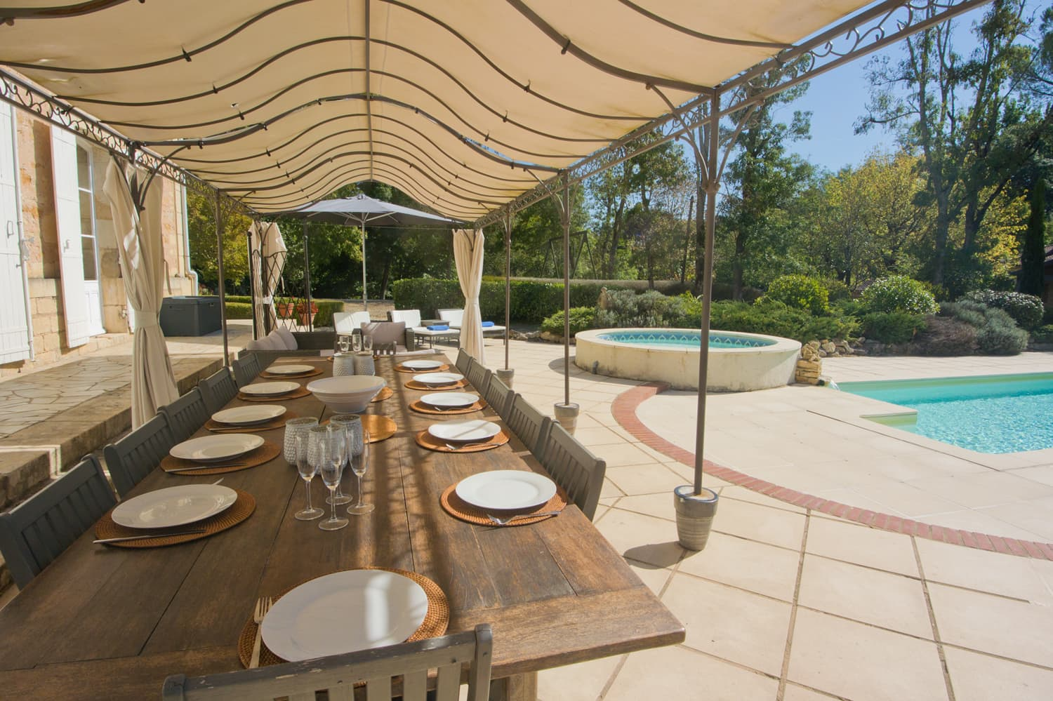 Shaded dining terrace beside private, heated pool